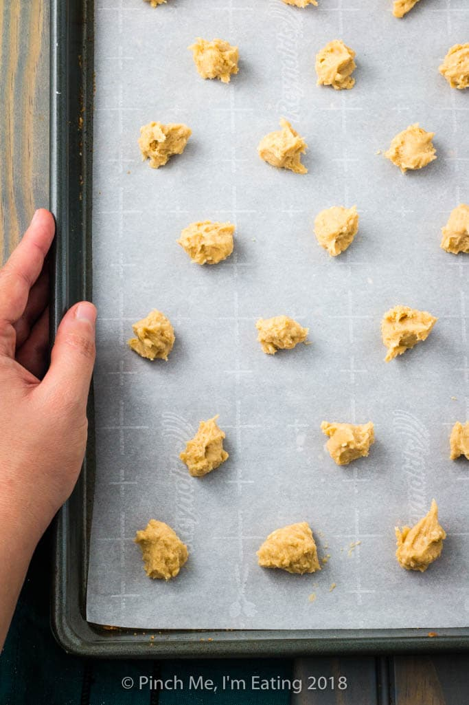 Uncooked balls of benne wafer dough on a parchment-lined cookie sheet