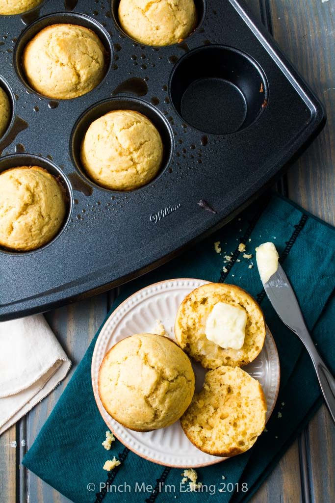 A cornbread muffin split open and buttered on a plate next to a muffin tin full of cornbread muffins