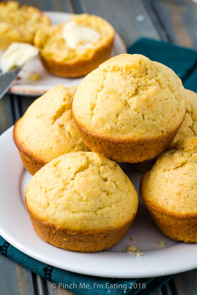 Five golden brown cornbread muffins stacked on a white plate