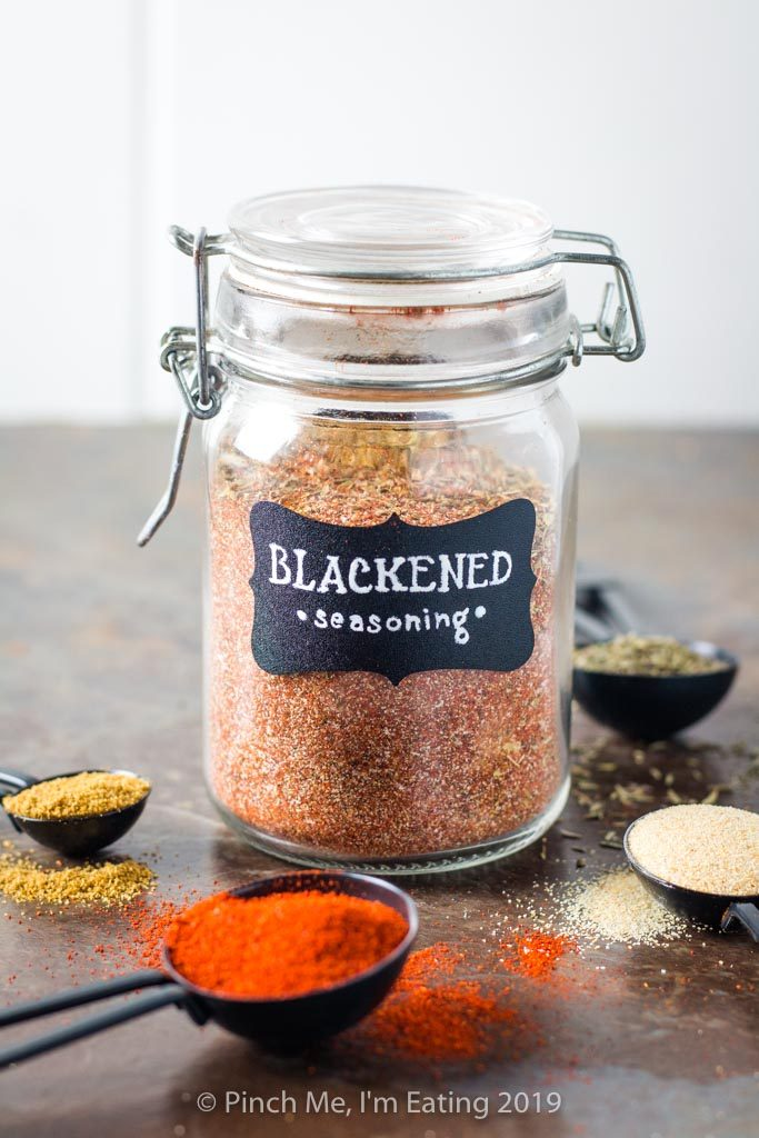 Glass jar of blackened seasoning with spices around it