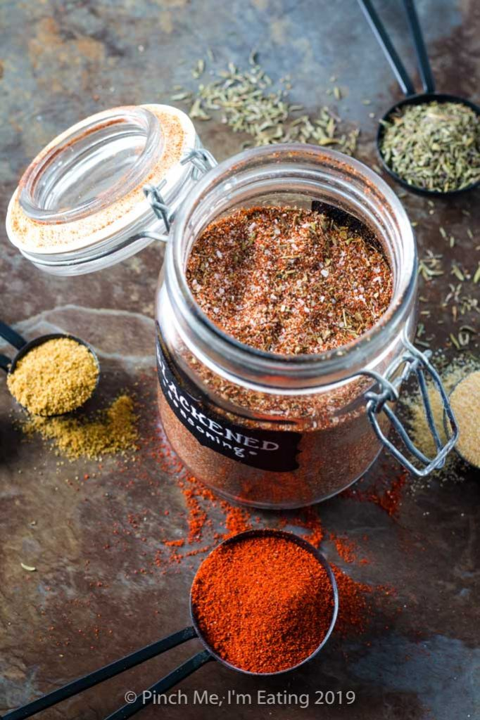 Three quarter view of blackened seasoning in glass spice jar surrounded by spices