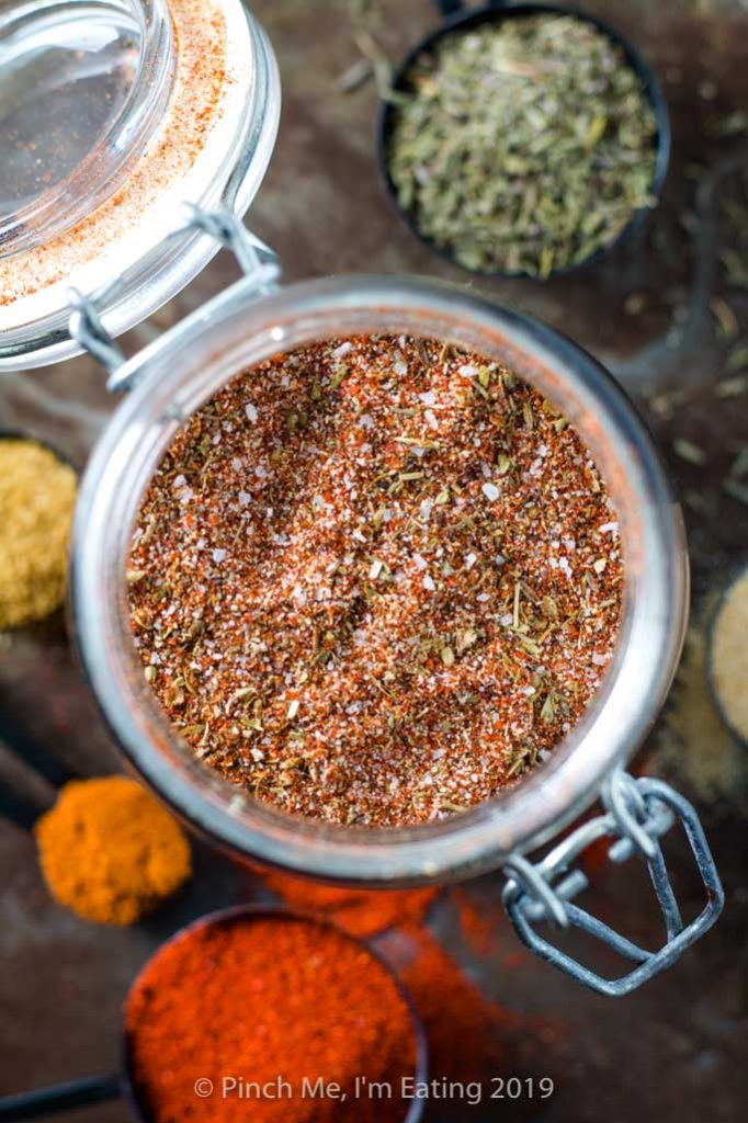 Overhead shot of blackened seasoning in glass jar with spices around it