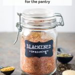 Blackened seasoning in glass spice jar surrounded by spices