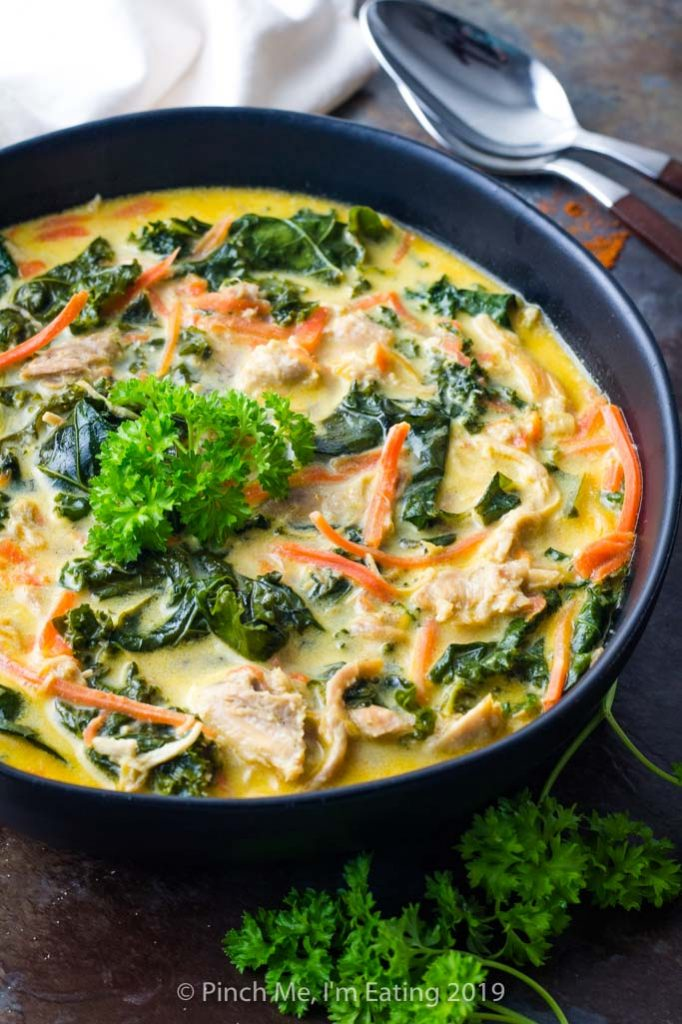 Three-quarter view of bowl of coconut curry soup with chicken, carrots and kale