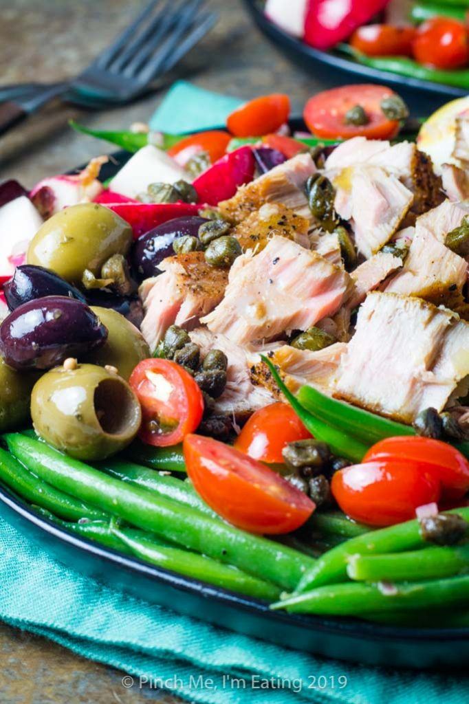 Side view of tuna Nicoise salad with green beans, tomatoes, and olives