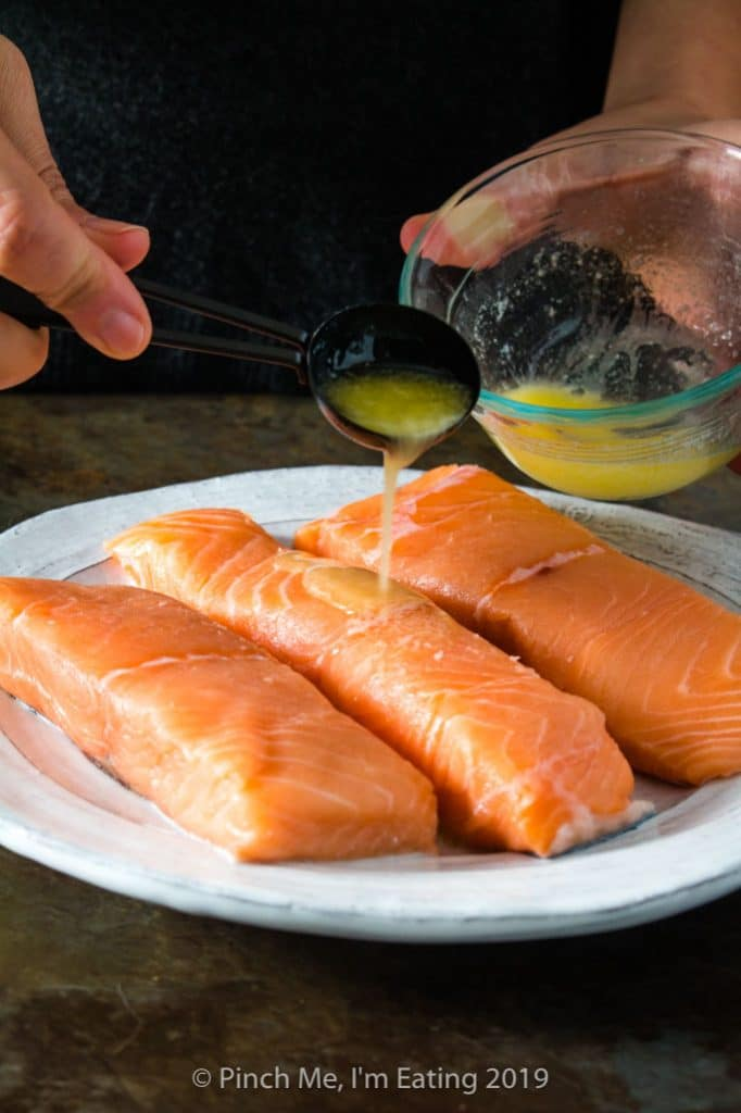 Drizzling butter on salmon fillets to make blackened salmon