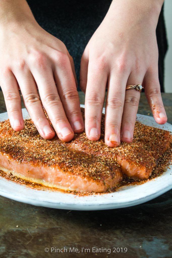 Patting blackening seasoning onto salmon fillets for blackened salmon