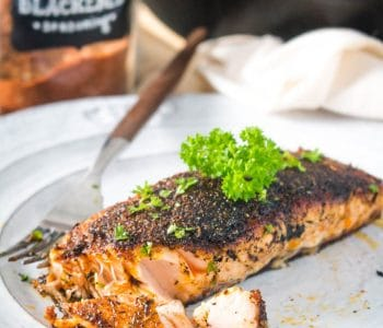 Flaky blackened salmon on a white plate