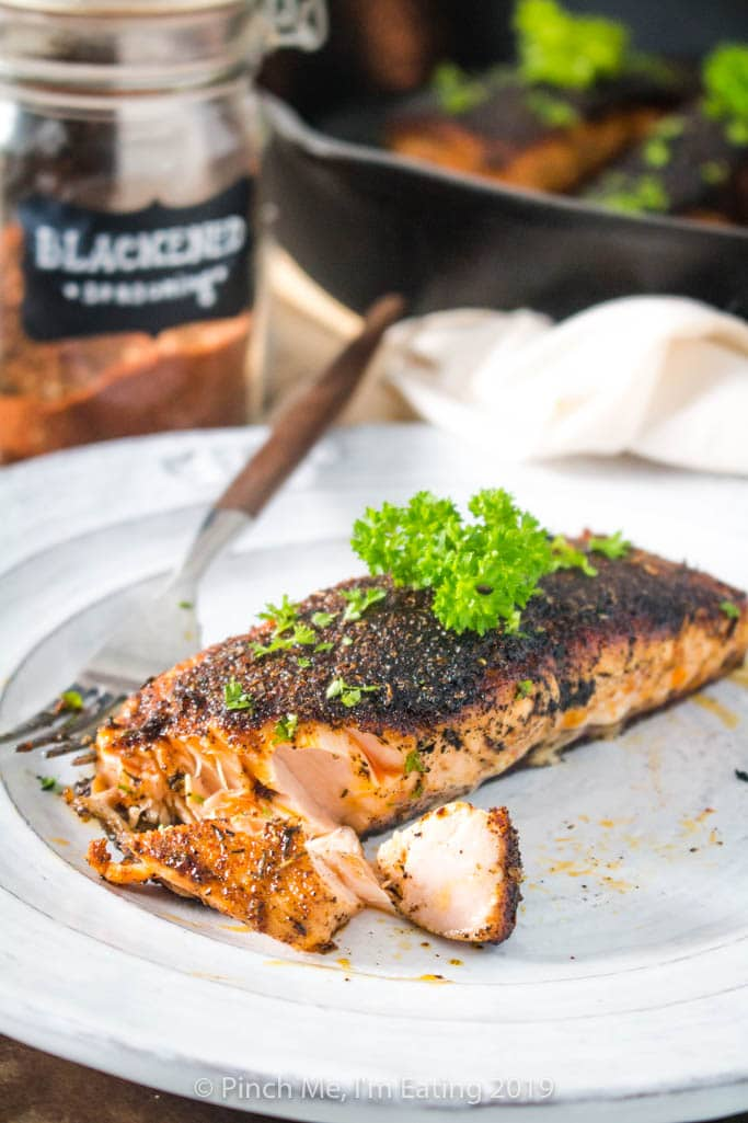 Flaky blackened salmon on a white plate