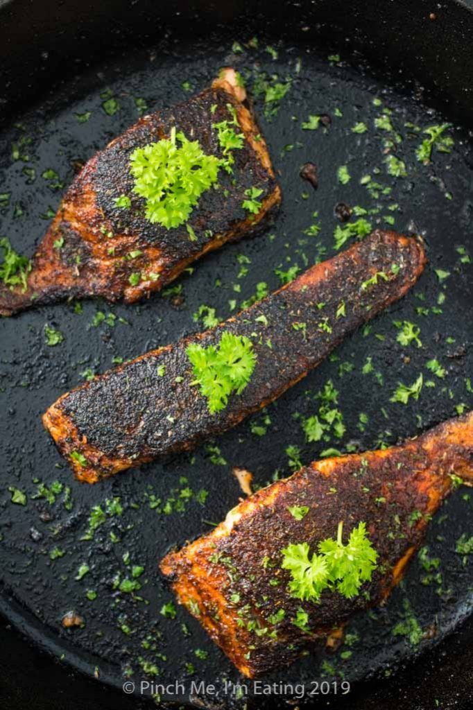Overhead shot of blackened salmon in a cast iron skillet