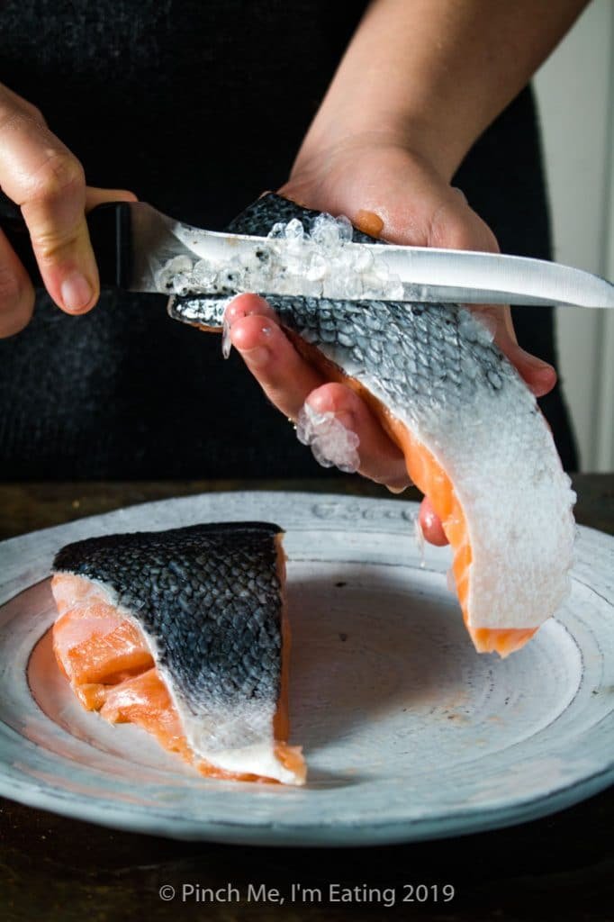 Process shot of taking scales off a salmon fillet