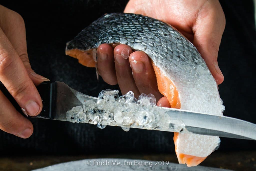 Process shot of descaling salmon fillets