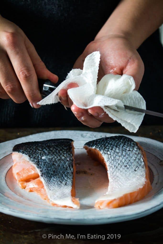 Process shot of descaling salmon fillets