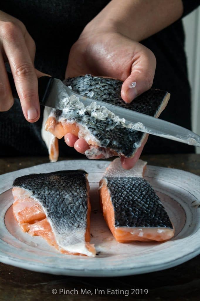 Process shot of descaling salmon fillets with a knife