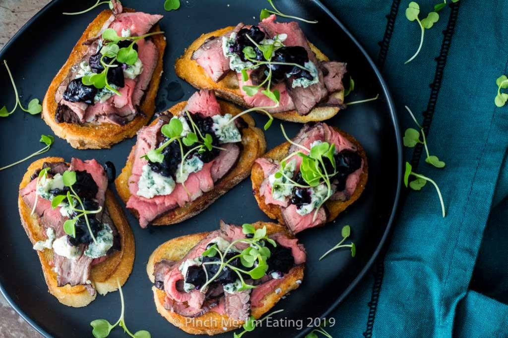 Flank steak crostini with blue cheese and blueberry caramelized onion jam and arugula microrgreens