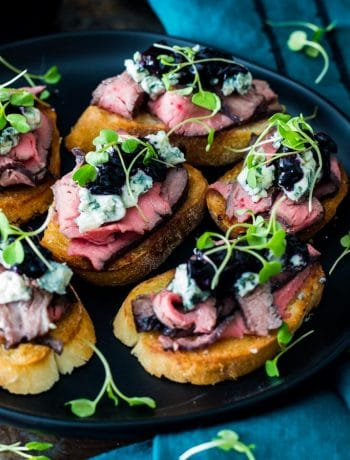 Flank steak crostini appetizers with blue cheese and blueberry caramelized onion jam