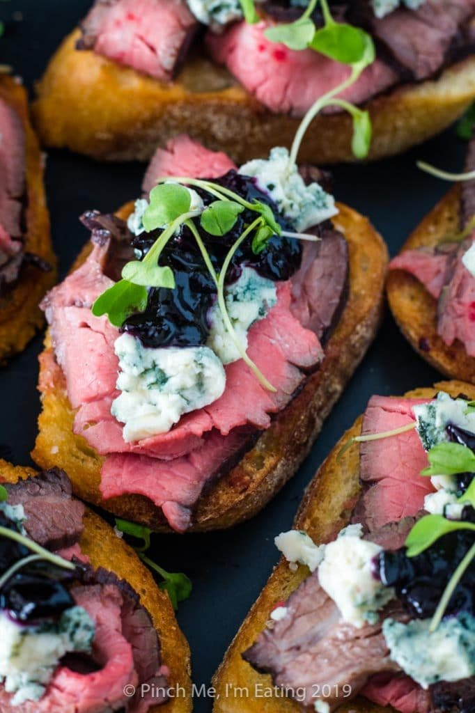 Medium rare flank steak crostini appetizers with blue cheese and blueberry caramelized onion jam and arugula microgreens