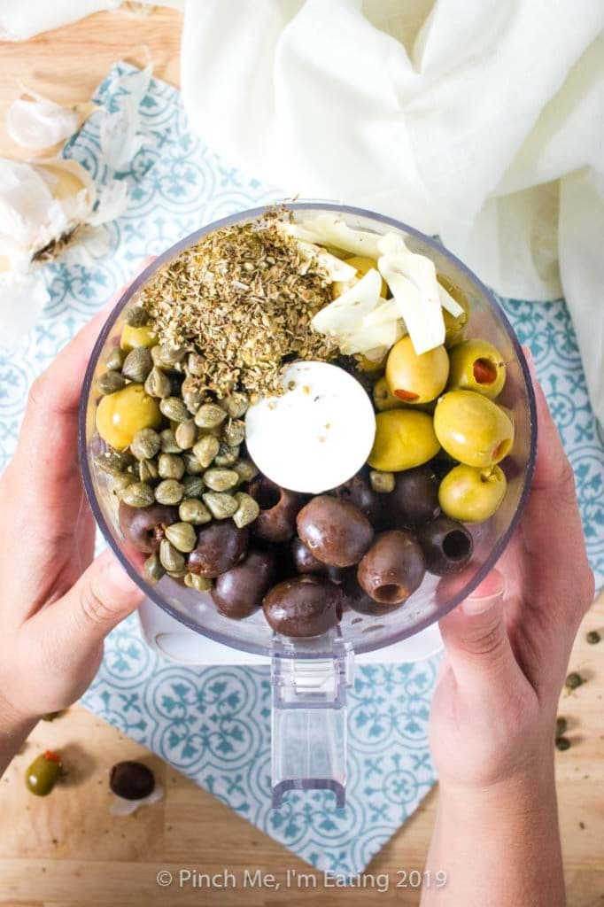 Black and green olives, capers, oregano, and garlic in a food processor
