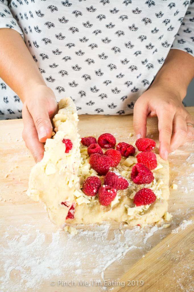 Folding white chocolate and raspberries into scone dough