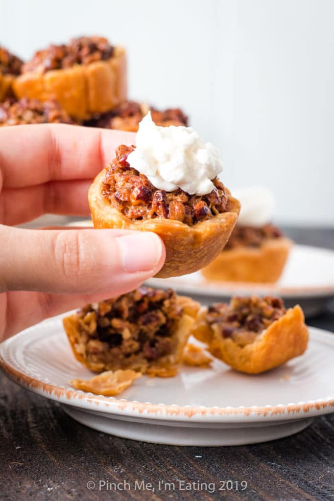 Hand holding bite-sized mini pecan pie