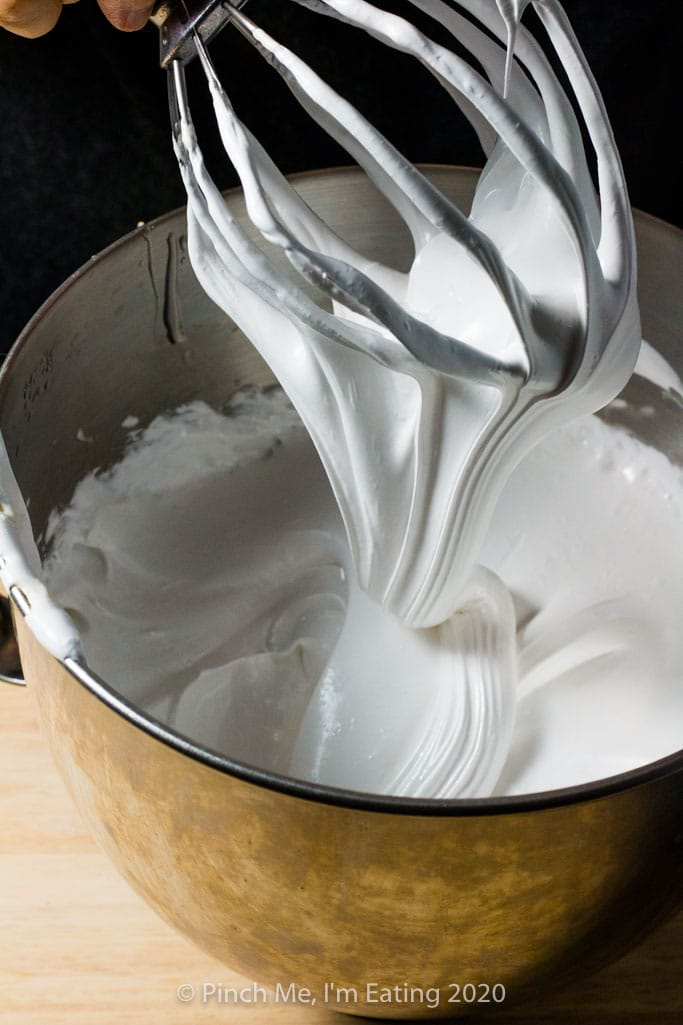 Homemade marshmallow mixture falls in a ribbon from a whisk attachment into a stainless steel bowl
