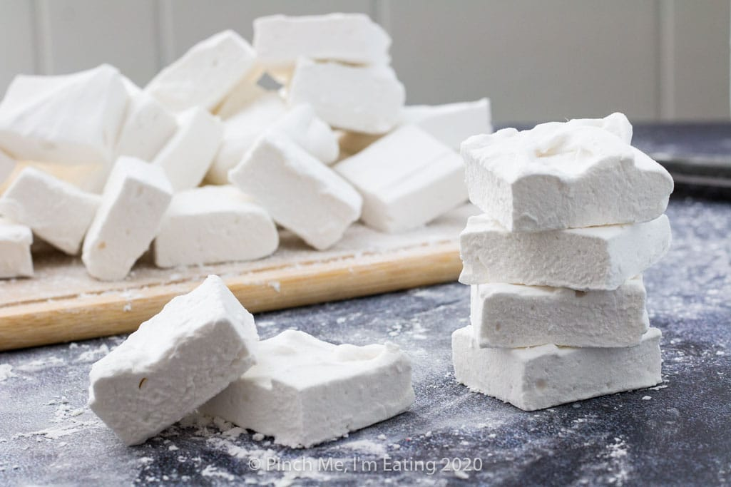 Several homemade marshmallows are stacked on a surface in front of a pile of marshmallows on a cutting board.
