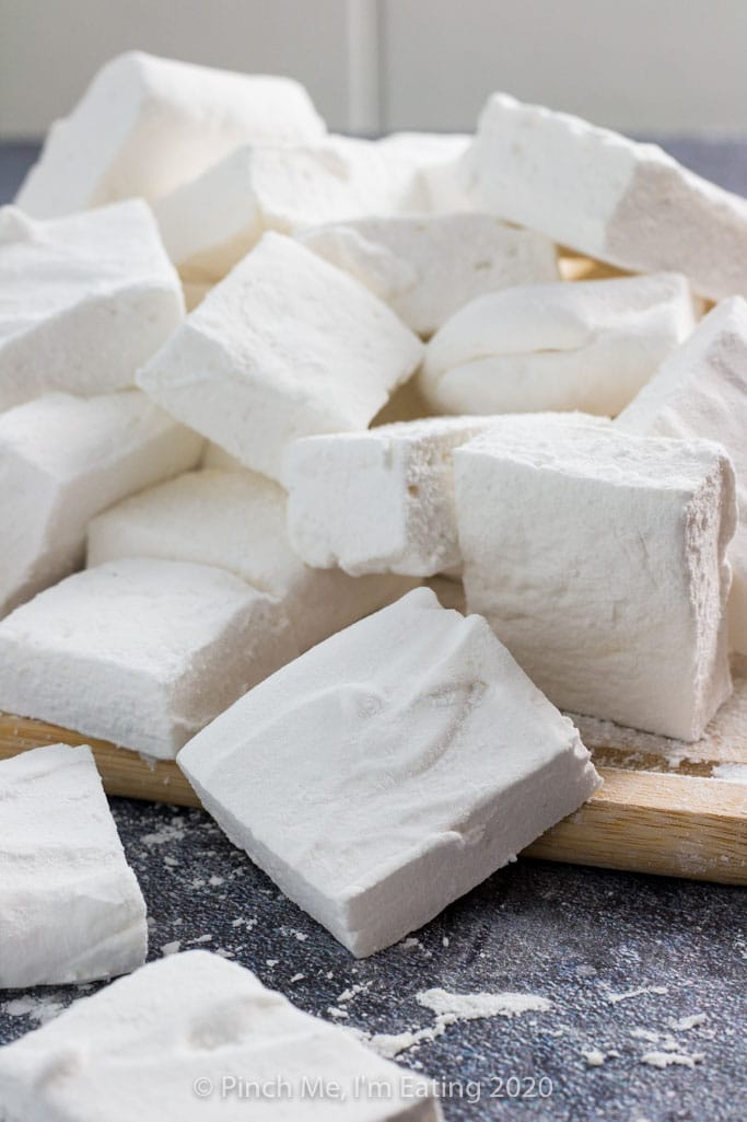 Homemade marshmallows in a pile on a wooden cutting board