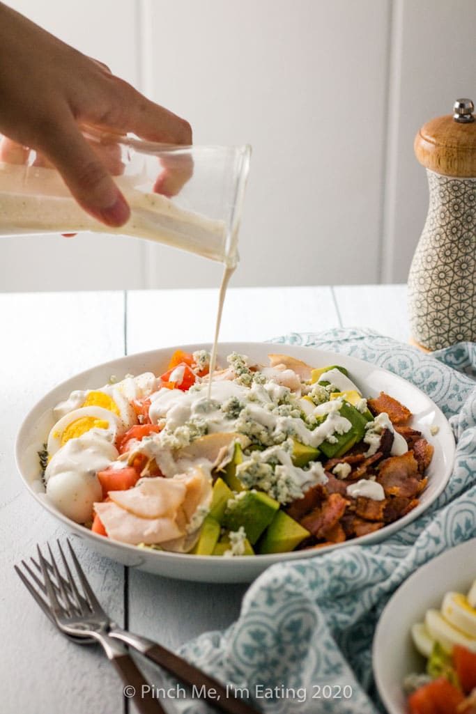 Turkey Cobb salad being drizzled with creamy blue cheese dressing