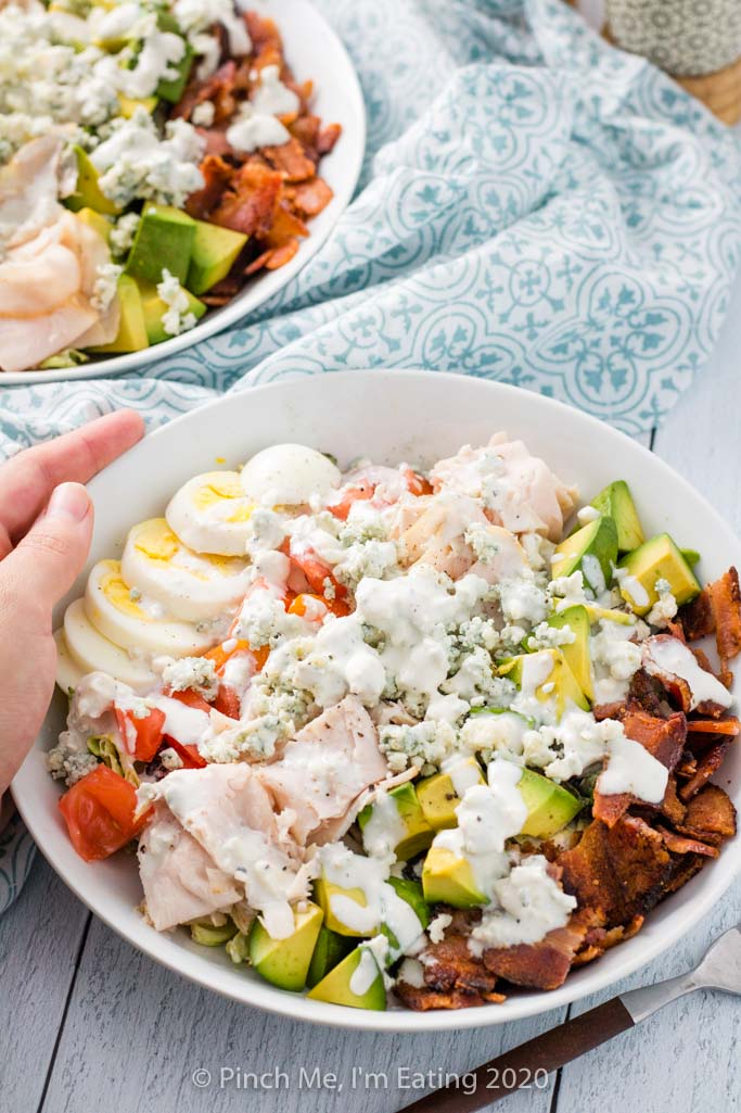 Overhead shot of turkey Cobb salad with bacon, avocado, turkey, blue cheese, tomato, and hard boiled egg in a white dish