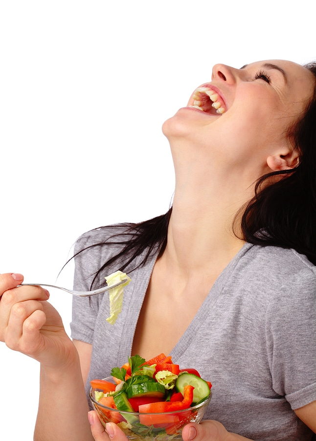 Laughing woman eating tiny salad with no dressing