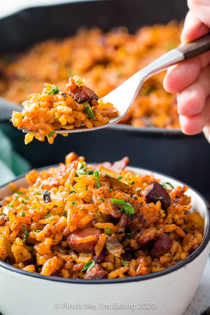 A fork lifts a bite Charleston red rice out of a small bowl of in front of a cast iron skillet