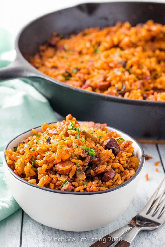 Charleston red rice in a white bowl in front of a cast iron skillet