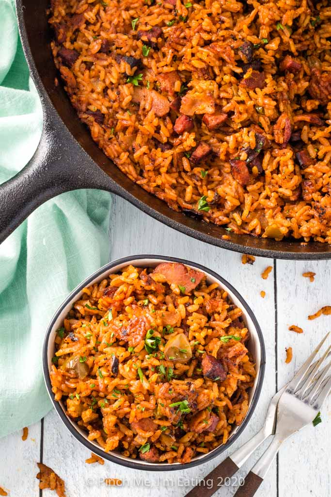 Overhead view of Charleston red rice with bacon and sausage in a cast iron skillet and small bowl with two forks