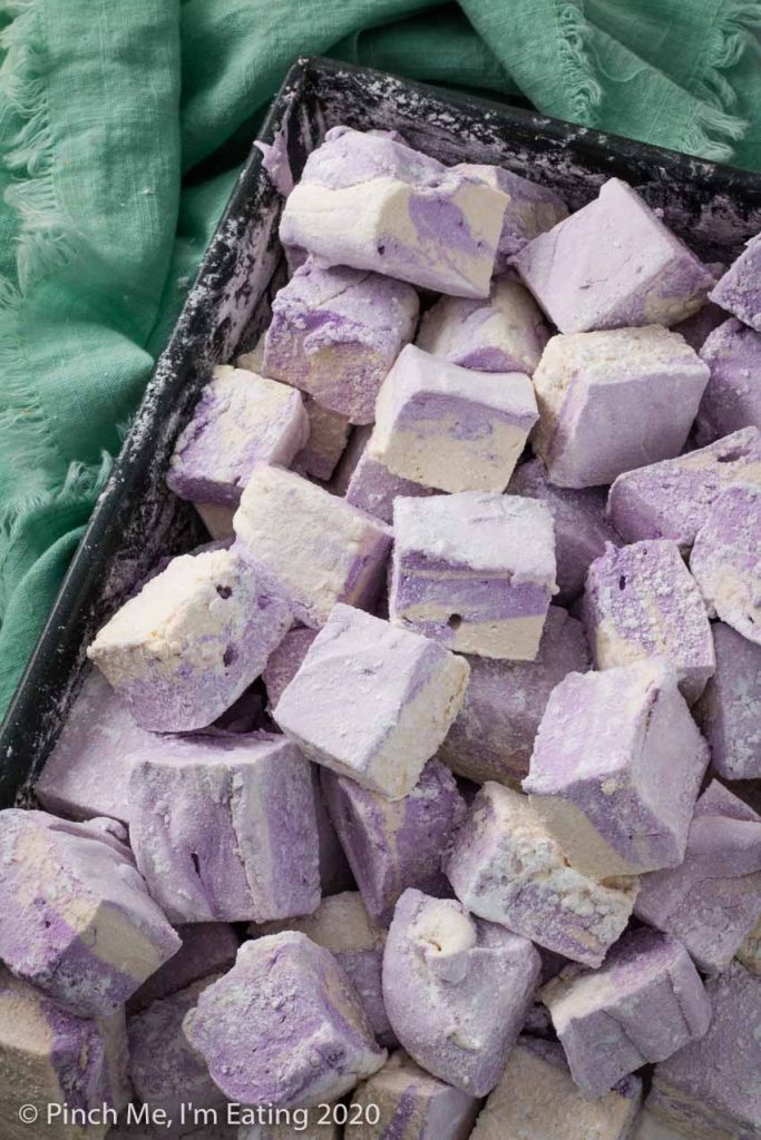 A baking pan full of purple and white swirled homemade Earl Grey marshmallows next to a blue-green fringed napkin