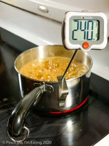 A small saucepan of boiling sugar syrup with a digital candy thermometer reading 240 degrees.