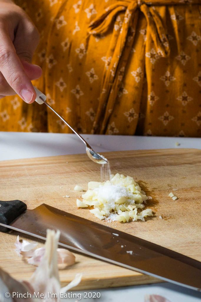 Hand pouring kosher salt onto pile of minced garlic on wooden cutting board
