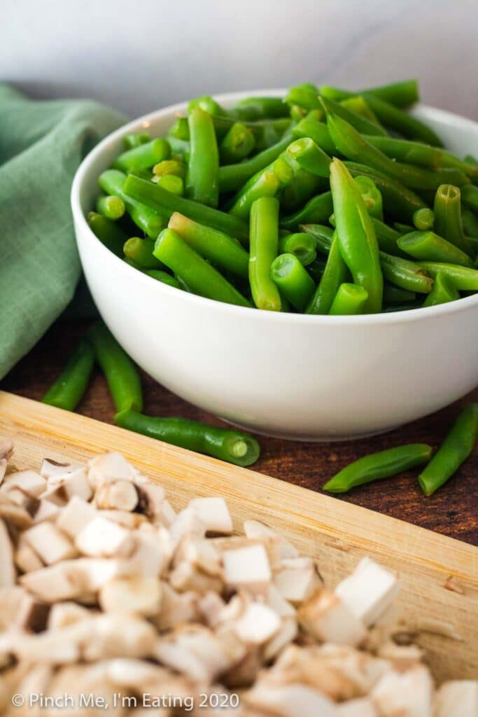 A white bowl of fresh blanched green beans with blurred mushrooms in the foreground