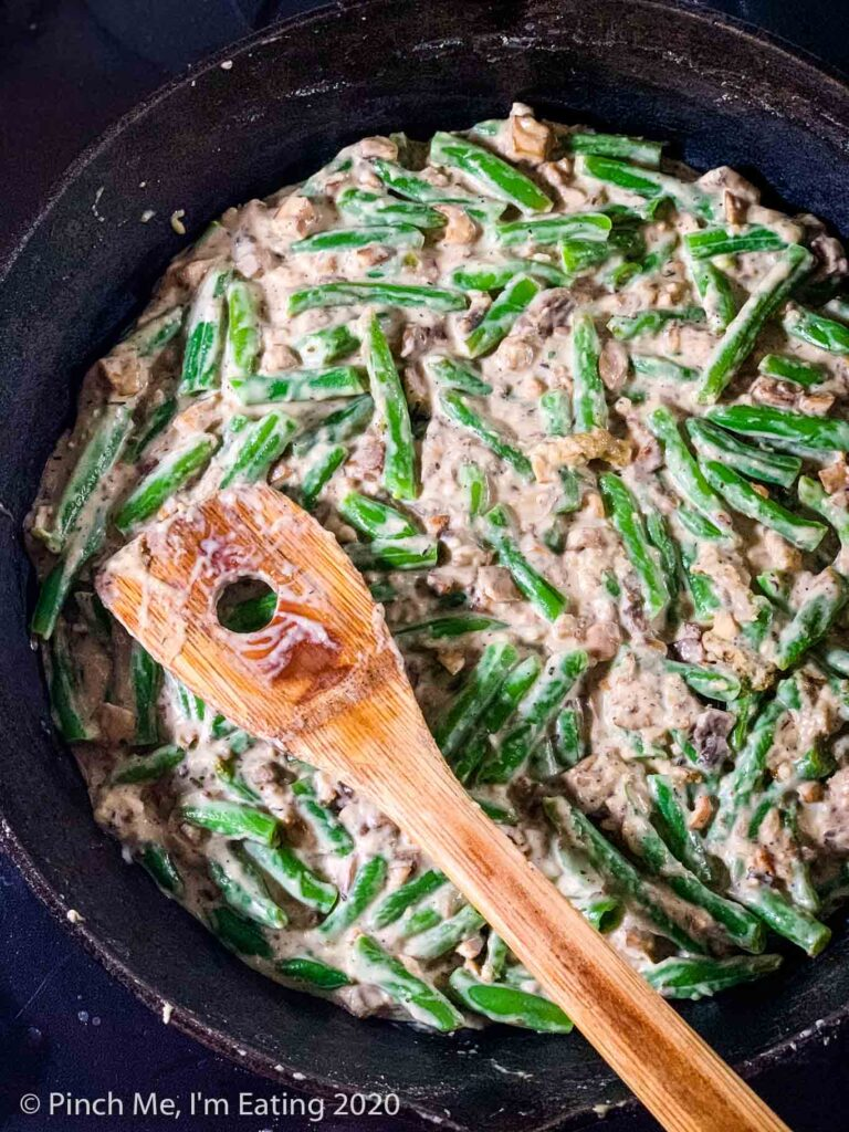 Fresh green beans mixed into homemade cream of mushroom soup in a cast iron skillet with a wooden spoon