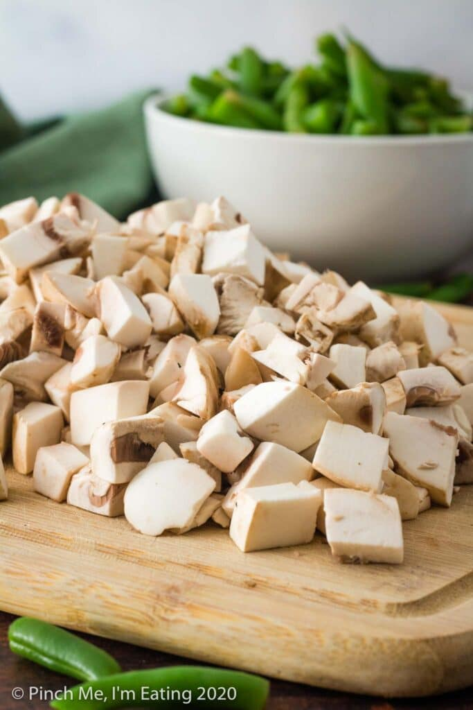Bamboo cutting board with a pile of diced mushrooms on it, with a white bowl of fresh green beans blurred in the background