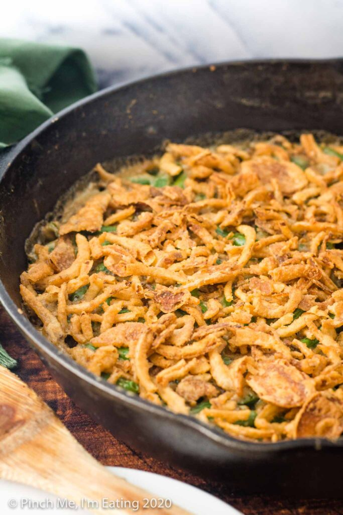 Cast iron skillet full of fresh green bean casserole topped with crispy fried onion topping
