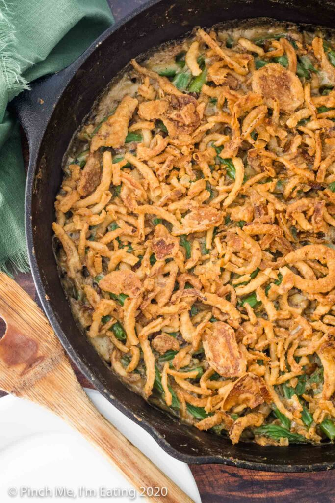 Overhead view of fresh green bean casserole topped with crispy fried onion topping in cast iron skillet with a wooden spoon