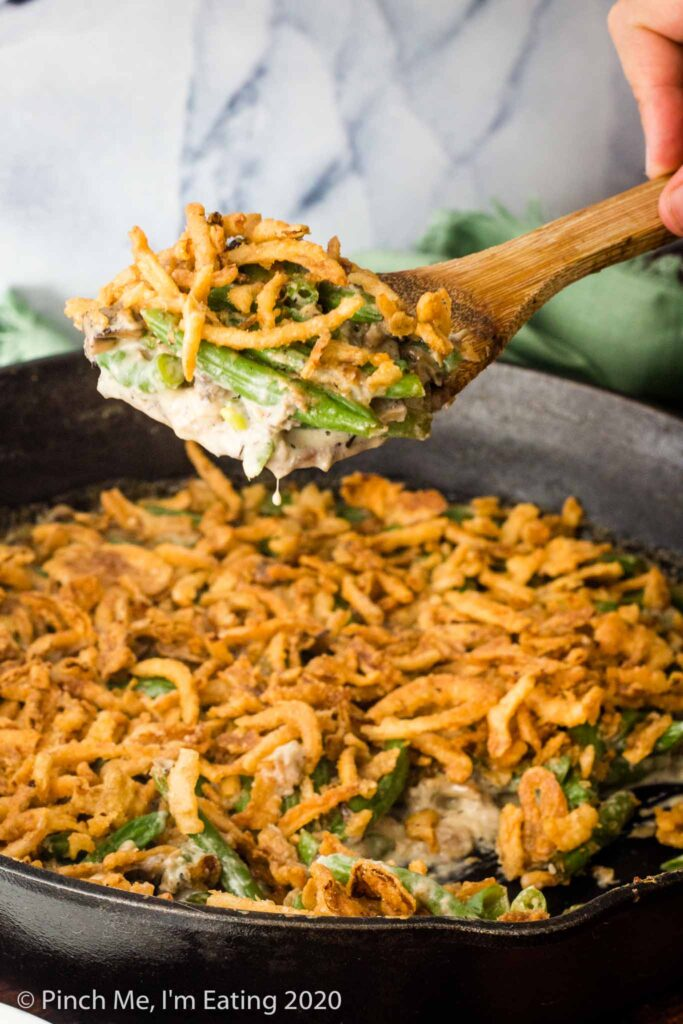A wooden spoon serving fresh green bean casserole out of a cast iron skillet