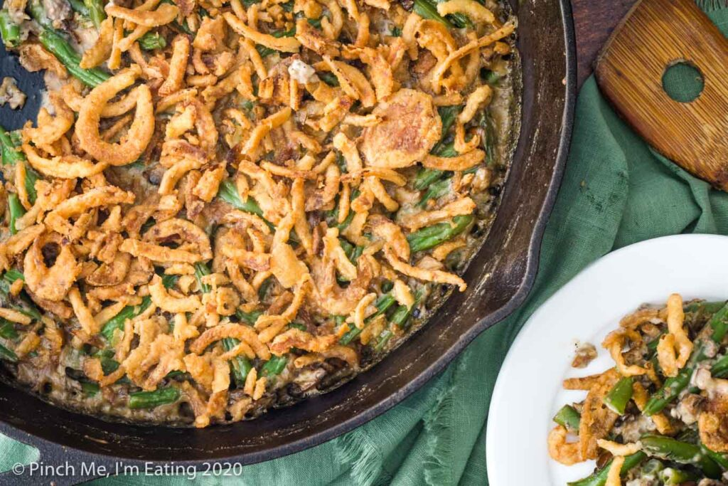 Overhead view of fresh green bean casserole in cast iron skillet with a single serving on a white plate and wooden spoon