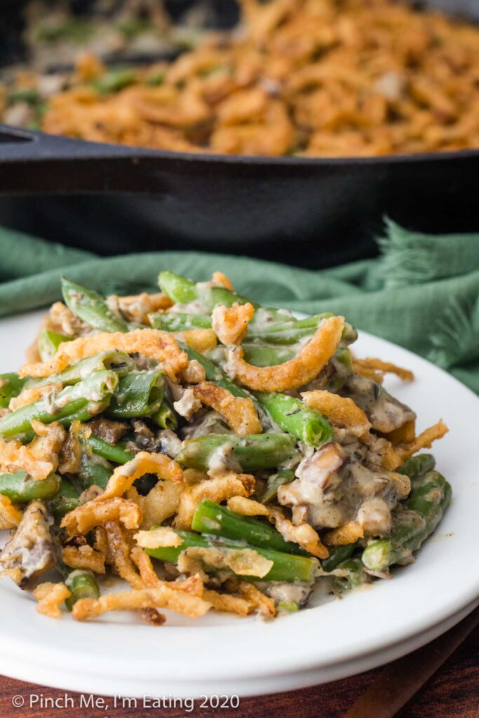 A serving of fresh green bean casserole on a small white plate