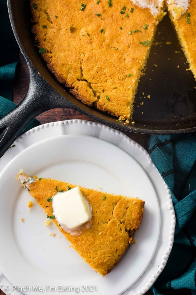 A wedge of cornbread with butter on top on a white plate next to a cast iron skillet of Southern buttermilk cornbread