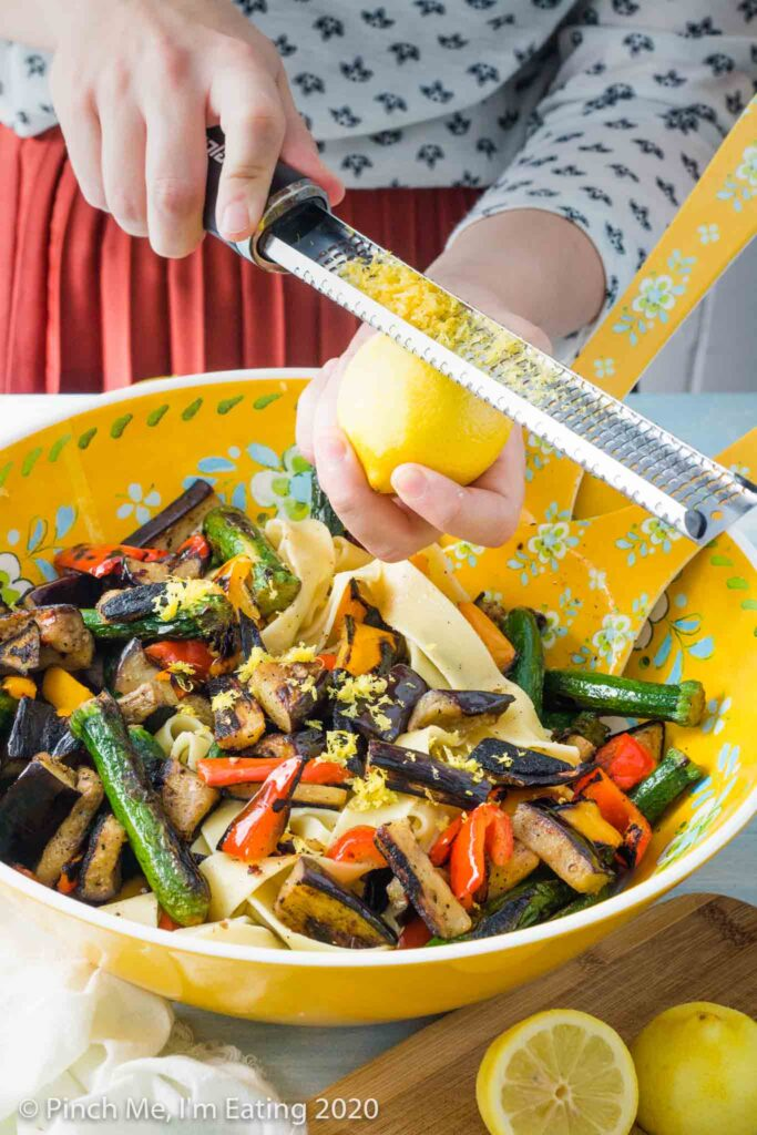 A woman zesting a lemon into a bowl of grilled vegetable pasta