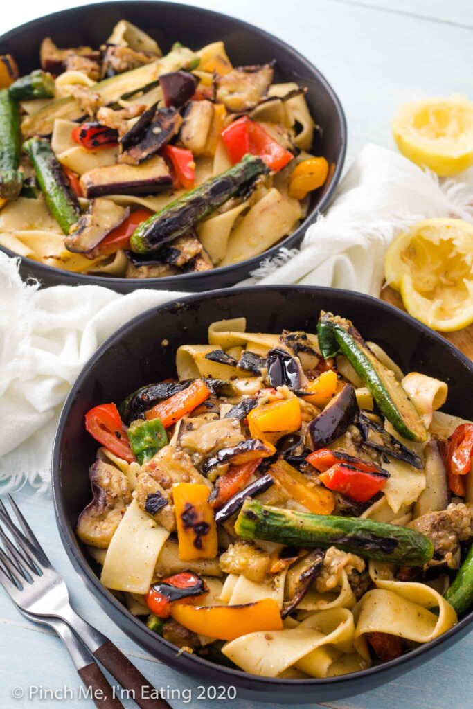 Two black bowls of pappardelle pasta with grilled vegetables