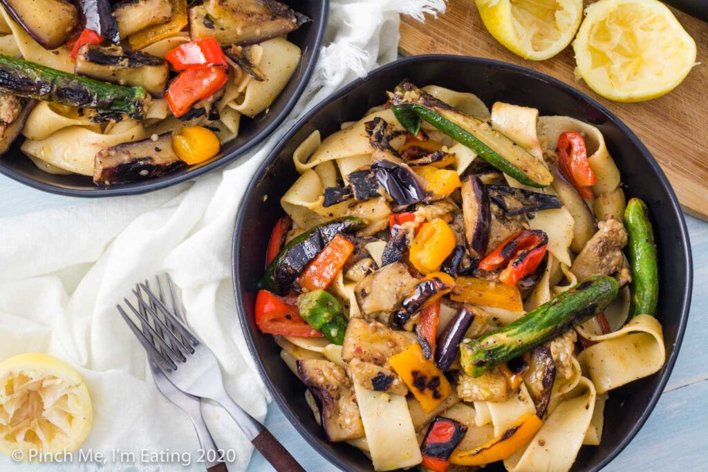 Overhead view of two black bowls of grilled vegetable pasta. A wooden cutting board with a cut lemon is in the corner.