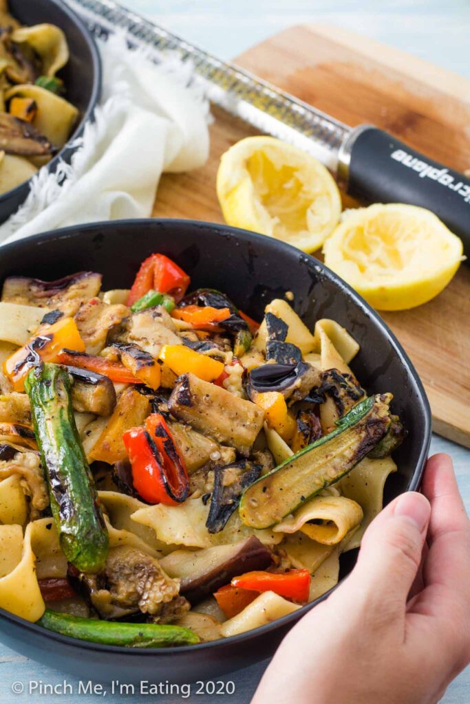 Hands holding a black bowl of pappardelle pasta with grilled vegetables. A cutting board with a lemon and zester are in the background.
