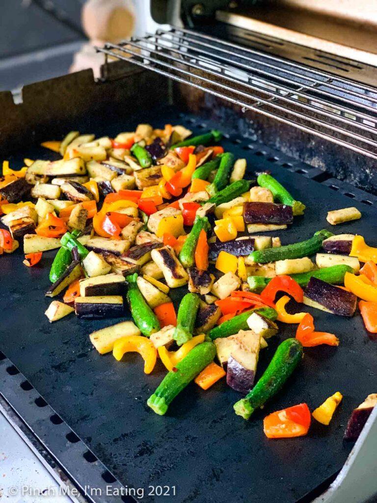Cut vegetables sautéeing on grill mats on a Weber grill